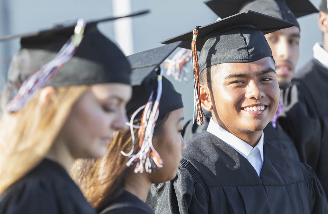 A group of multi-ethnic students graduating from high school or college, standing in a row outdoors, wearing black caps and gowns, holding diplomas. The focus is on the Asian / Pacific Islander young man in the middle, looking at the camera.